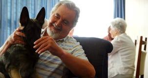 Senior man petting his dog at retirement home 4k