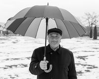 Smiling senior man. Photo of smiling senior man under umbrella walking in the park Royalty Free Stock Image
