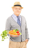 Smiling senior man posing with a dish full of healthy vegetables Stock Images