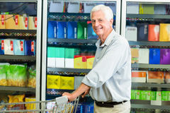 Smiling senior man pushing cart royalty free stock photo