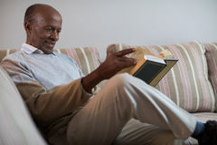 Smiling senior man reading book at home. Smiling senior man reading book while sitting on sofa at home Stock Image