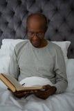 Smiling senior man reading book while sitting on bed Royalty Free Stock Image