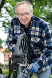 Smiling senior man repairing a bicycle Royalty Free Stock Images