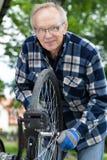Smiling senior man repairing a bicycle royalty free stock images