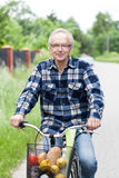 Smiling senior man riding a bicycle. With a basket of shopping Royalty Free Stock Photography