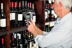 Smiling senior man scanning wine bottles Royalty Free Stock Photos