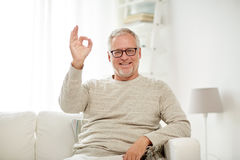 Smiling senior man showing ok hand sign at home Stock Image