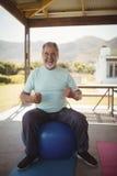 Smiling senior man sitting on fitness ball. Portrait of smiling senior man sitting on fitness ball at veranda Royalty Free Stock Images