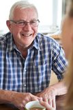 Smiling Senior Man Sitting In Kitchen Talking With Woman At Home royalty free stock photos