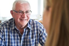 Smiling Senior Man Sitting In Kitchen Talking With Woman At Home stock image