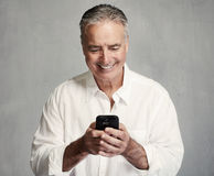 Smiling senior man with smartphone stock photos