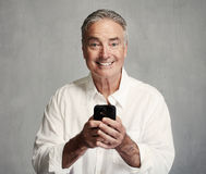 Smiling senior man with smartphone stock photo