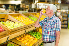 Smiling senior man smelling orange stock photography