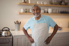 Smiling senior man standing with hand on hips in kitchen Royalty Free Stock Photos