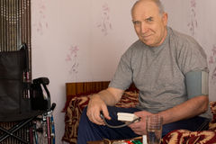 Smiling senior man taking his blood pressure Royalty Free Stock Photos