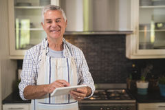Smiling senior man using digital tablet in kitchen at home Royalty Free Stock Photo