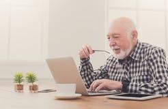 Smiling senior man using laptop copy space Stock Image