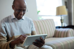 Smiling senior man using tablet. While sitting on sofa at home Stock Photo