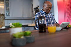Smiling senior man using tablet. While sitting at table in kitchen Royalty Free Stock Photo