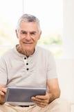 Smiling senior man using tablet. On the sofa Royalty Free Stock Photos