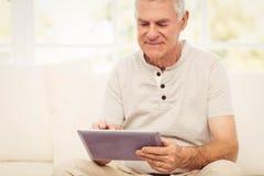 Smiling senior man using tablet. On the sofa Royalty Free Stock Image