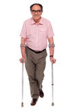 Smiling senior man walking with two crutches. All on white background Stock Photos