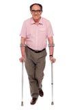 Smiling senior man walking with two crutches Stock Photos