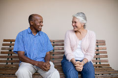 Smiling senior man and woman looking at each other while sitting on bench against wall. Smiling senior men and women looking at each other while sitting on bench Stock Photography