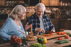 Smiling senior man and woman making salad together stock photography