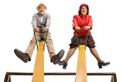 Smiling senior man and woman sitting on a seesaw stock photo