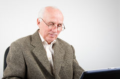 Smiling senior man working on laptop Stock Images