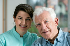 Smiling senior man and young nurse Stock Photography