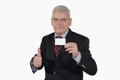 Smiling senior manager with card posing thumbs up. A smiling senior caucasian manager showing a business card with copy space and posing with the thumbs up sign Royalty Free Stock Images