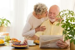 Smiling senior man reading newspaper and his wife kissing him royalty free stock photo