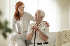 Smiling senior man with walking stick and his happy granddaughte royalty free stock photos