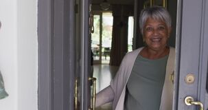 Smiling senior mixed race woman opening front door and welcoming