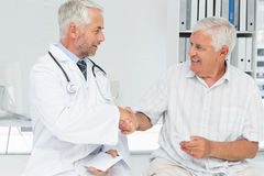 Smiling senior patient and doctor shaking hands Royalty Free Stock Photos