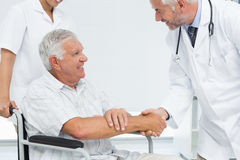 Smiling senior patient and doctor shaking hands Stock Image