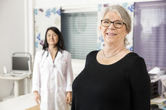Smiling Senior Patient Standing With Doctor In Background stock photography