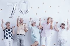Smiling senior people celebrating with silver balloons. During birthday party Royalty Free Stock Photos