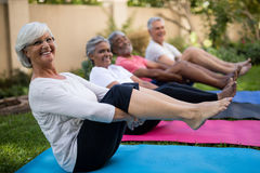 Smiling senior people exercising with feet up. Over mats at park Stock Photography