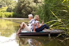 Smiling senior people. Portrait of happy couple fishing at the lake. Elderly people sitting back to back on pier and looking at camera while senior women holding Stock Photos