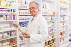 Smiling senior pharmacist holding envelope and prescription Royalty Free Stock Image