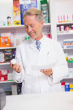 Smiling senior pharmacist holding prescription and jar Stock Photography