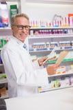 Smiling senior pharmacist holding prescription Stock Photos