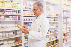 Smiling senior pharmacist reading prescription Royalty Free Stock Images