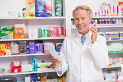 Smiling senior phoning while reading prescription Royalty Free Stock Photography