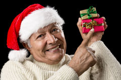 Smiling Senior Pointing At Two Wrapped Xmas Gifts. Elderly man with red Santa Claus cap and warm pullover. His raised right index finger is pointing at a red and Stock Image