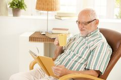 Smiling senior relaxing at home with book and tea Stock Image