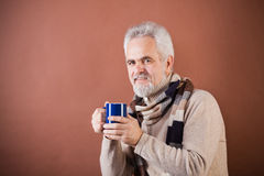 Smiling senior in scarf with a cup. Studio shot of a smiling senior in striped scarf holding a blue cup Royalty Free Stock Photo